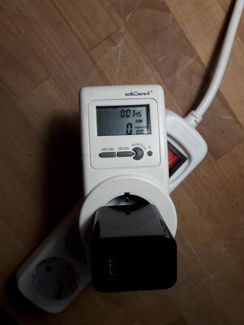 Ein Strommesgerät aus dem Baumarkt mit eingestecktem Netzteil zeigt 0W an.