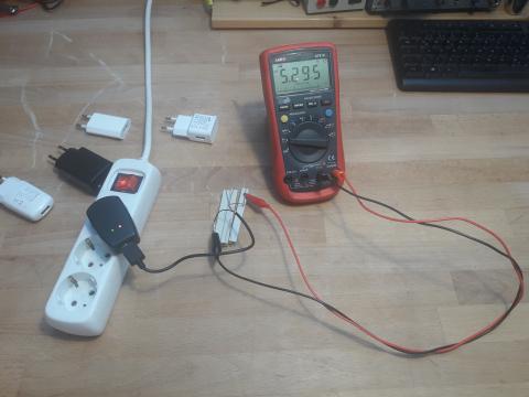 Ein Handynetzteil ist in die Steckdose eingesteckt. Über ein aufgeschnittenes USB Kabel ist ein Widerstand angeschlossen. Am Widerstand ist mit Krokoklemmen ein Spannungsmessgerät angeschlossen.