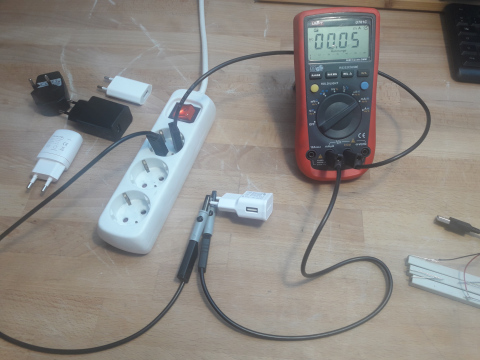Ein Digitales Multimeter ist in Serie mit einem Handynetzteil geschalten und in die Steckdose eingesteckt. Es zeigt 0,05mA.